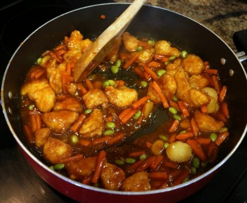 stirring orange chicken while it is cooking in a  pan on the stove