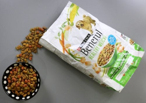 A bag of purina beneful healthy weight being poured into a black dog dish