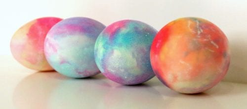 four hard boiled eggs that have been dyed in shaving cream and food coloring lined up