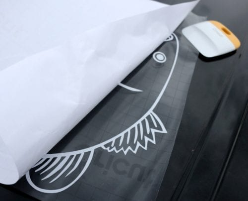 Vinyl Car Window Decal Sticker with Cricut Explore featured by top US craft blog, The Crafty Blog Stalker removing the paper backing from the car window decal