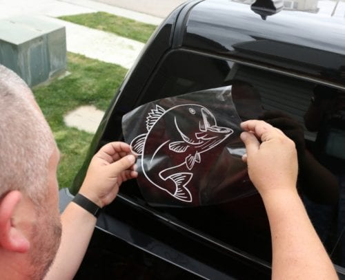 Vinyl Car Window Decal Sticker with Cricut Explore featured by top US craft blog, The Crafty Blog Stalker a man positioning the car decal carefully on the back window of his truck