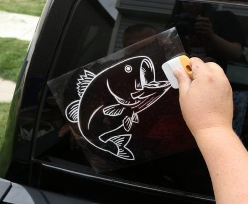 applying a bass fish vinyl car window decal sticker to the back of a truck