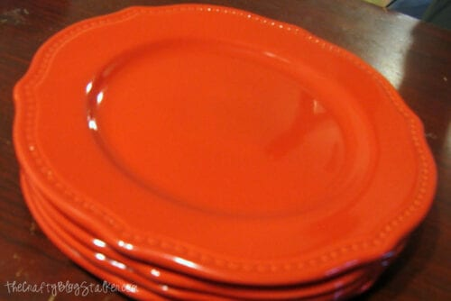 a stack of red ceramic plates