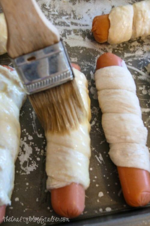 brushing egg onto pretzel dogs before baking