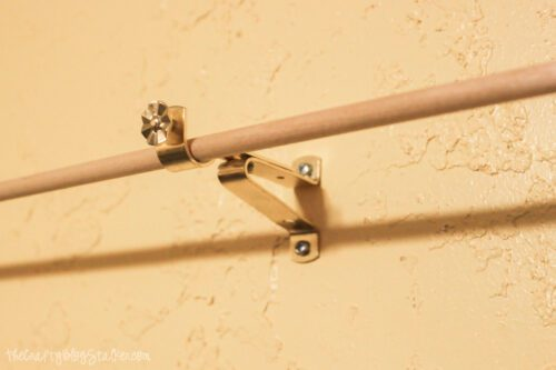 installing dowels to hold ribbon on a craft room wall