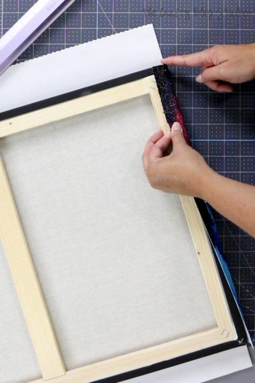 How to Frame Diamond Art | Easy DIY Craft Tutorial Idea | Diamond Art Club | Painting with Diamonds | Home Decor | Framing | Sparkle | How to Frame Diamond Art by popular US craft blog, The Crafty Blog Stalker: image of a woman folding over the edges of her diamond artwork on the canvas.