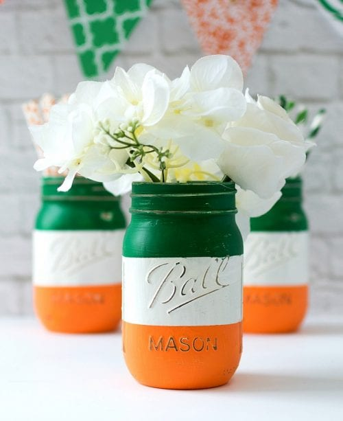 a close up of ball mason jars painted with the irish flag colors