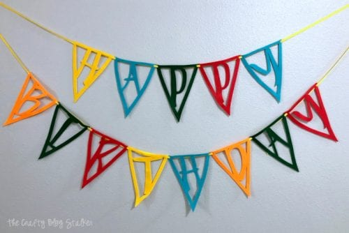 Felt Happy Birthday Pennant Banner hung on a light gray wall