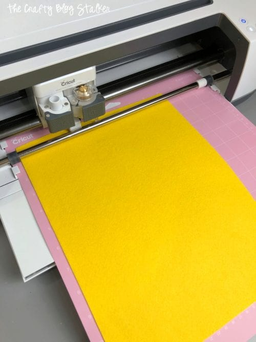 Cricut Maker cutting a sheet of yellow craft felt
