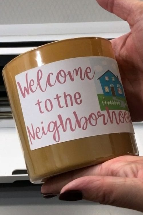 two hands holding a neighbor gift of a candle with a print then cut sticker