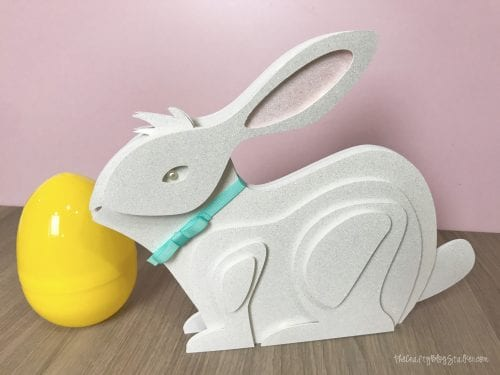 finished layered paper art bunny with a pink background with a yellow plastic easter egg