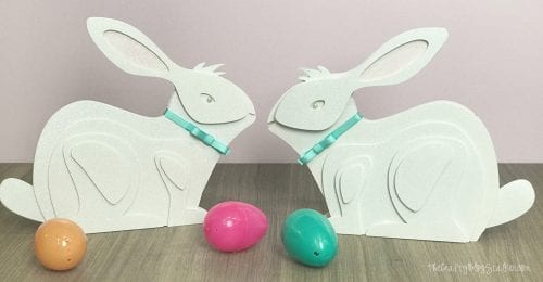 two finished layered paper art bunnies with a plastic easter eggs