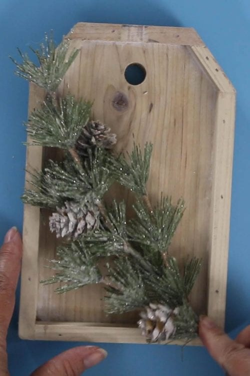 winter pine floral pick pressed into place on a wood tag