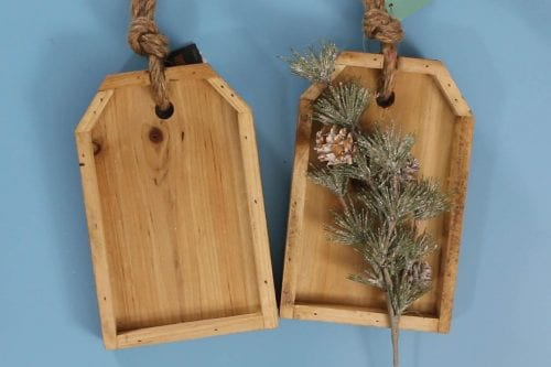 two wooden tags with a floral winter pine pick