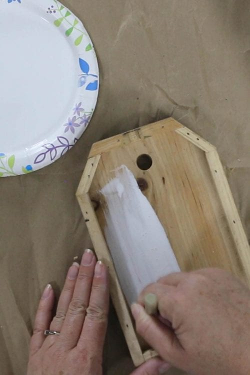 removing extra white paint with a paper towel
