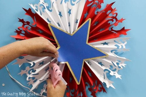 using hot glue to secure the star for the Large DIY Patriotic Paper Rosette