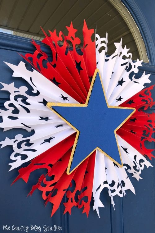 Large DIY Patriotic Paper Rosette hanging on a blue front door