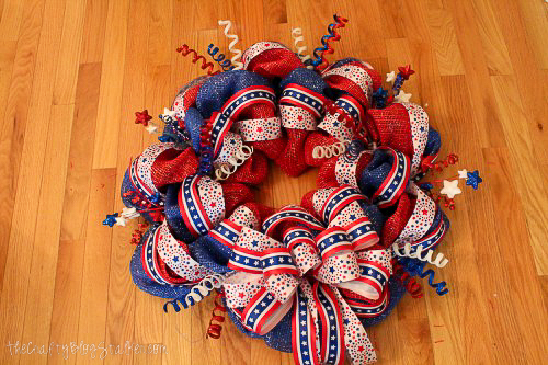 adding a ribbon bow to a patriotic mesh wreath