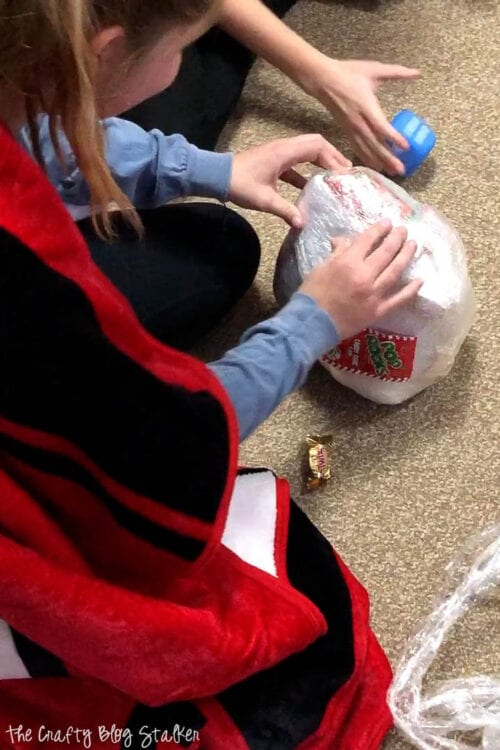 a girl trying to unwrap the prize ball