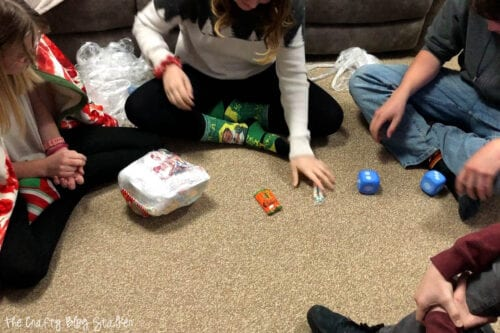 a group of teenagers in a circle on the floor playing a christmas game