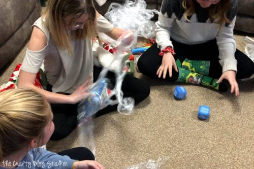 a girl unwrapping the prize ball while another girl rolls dice