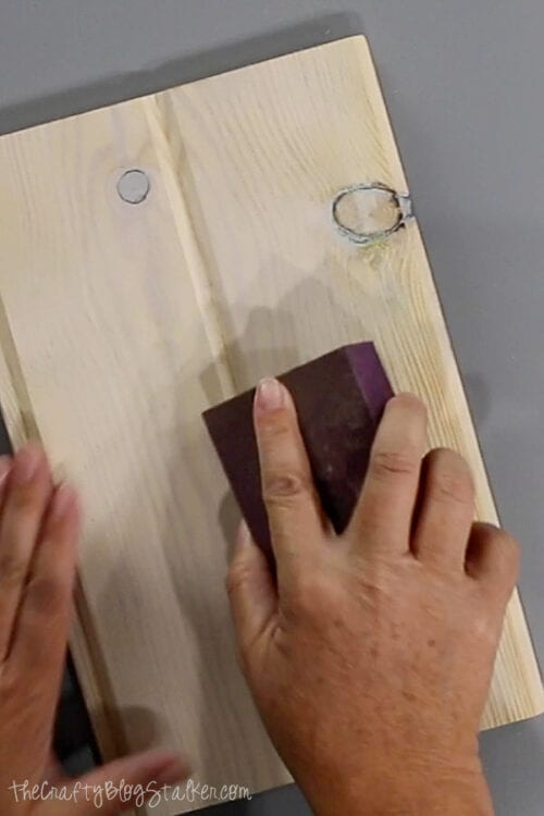 sanding the wood piece with a block sander