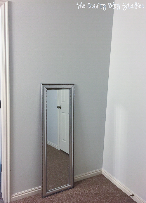 an empty wall with a small mirror leaned against it