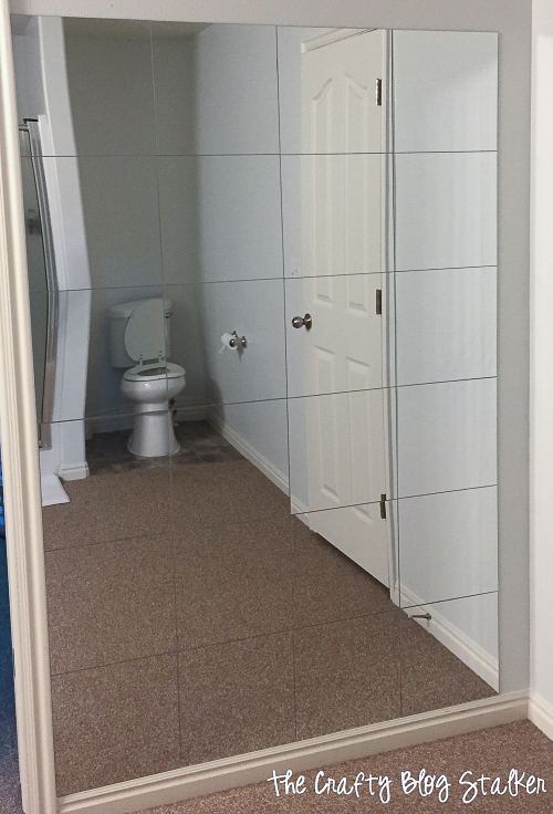 a mirror wall showing the reflection of the toilet
