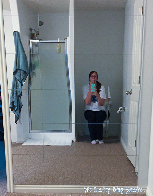 a girl sitting on the toilet in front of the mirror wall