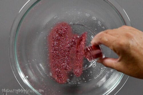 adding glitter to clear glue and water to make slime