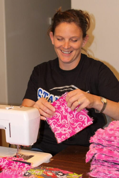 a woman sewing fabric squares together