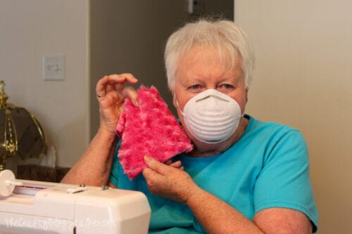 grandma holding minky fabric square with a face mask on