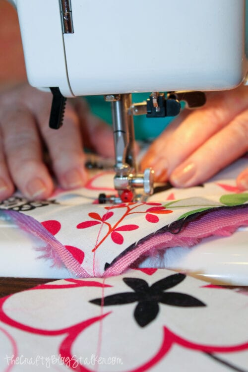 sewing an x into the layers of fabric squares