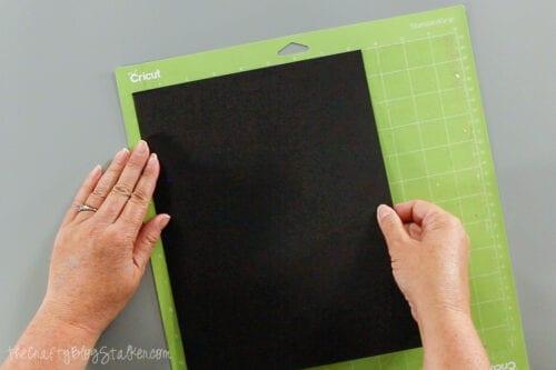placing black cardstock on a standard grip mat