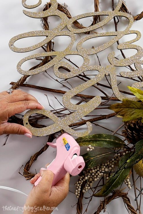 """using a a hot glue gun to secure the """"happy fall"""" wood piece in place"""