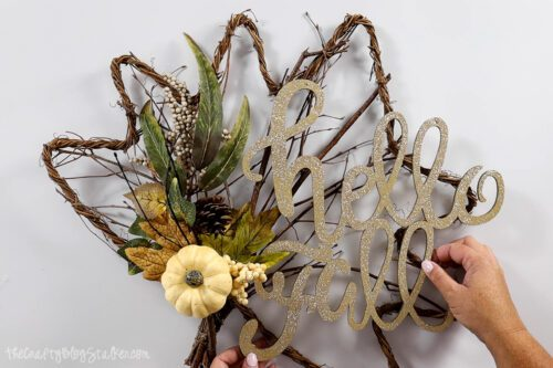 """arranging """"hello fall"""" wood piece on the rattan leaf"""