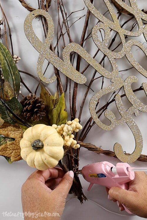 using a hot glue gun to secure fall floral pick in place